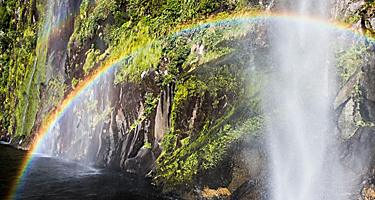 A rainbow shining over a waterfall in New Zealand