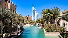 The Burj Al Arab with palm trees and water seen from Madinat Jumeirah in Dubai, United Arab Emirates