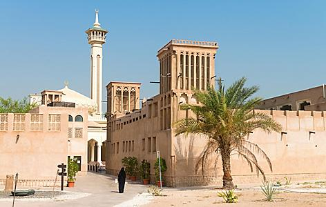 Woman in traditional muslim black dress in old arabic city district with mosque minaret in Al Fahidi Historical District of Dubai