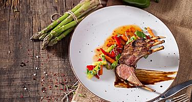 Lamb chops with vegetables served over a white plate