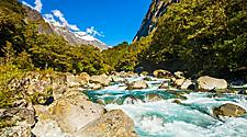 Beautiful turquoise creek with snowy peaks near the Milford highway in Dusky Sound, New Zealand