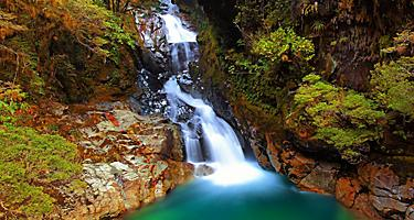 Falls Creek with a waterfall flowing over the mountain in the National Fiordland Park, New Zealand