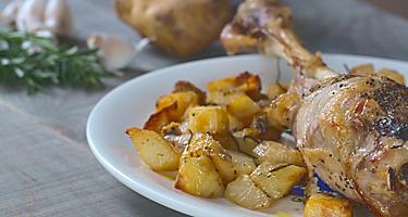 A baked leg of lamb on a white plate with a side of potatoes
