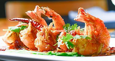 Four fried shrimp on a white plate