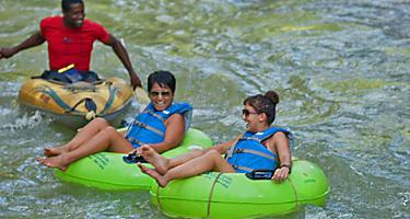 Two people tubing down a river with a guide
