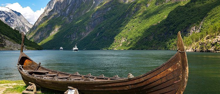 A replica viking boat with mountains in the background