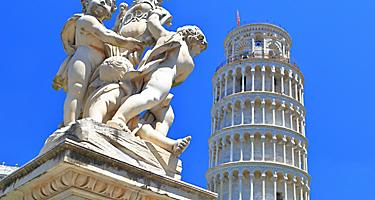A marble statue with the Leaning Tower of Pisa in the background