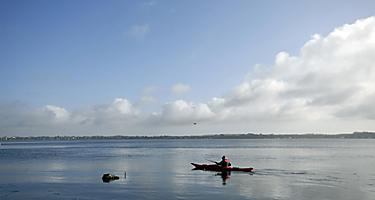 A person kayaking in the bay in Demark
