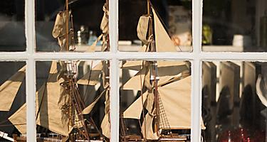 Window display of storefront with a model ship and other antiques in Galveston, Texas