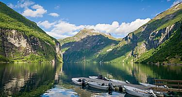 Multiple small boats docked at a pier in Geiranger, Norway,