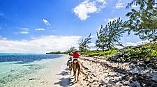 People riding horseback on the beach, George Town, Grand Cayman.