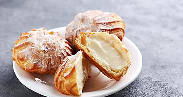 Four profiteroles cream pastries on a white plate