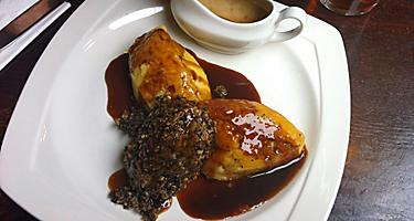 A white plate with haggis and gravy