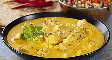 Indian pork curry in a creamy sauce served with naan bread, salad, and rice