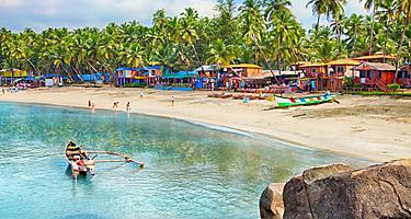The Palolem Beach with colorful beach huts and palm trees along the coast of Goa, India