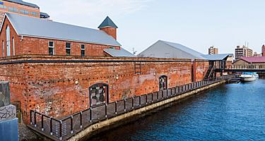 Kanemori red brick warehouse, bay-side godowns,  and ferry boat in Hakodate, Japan