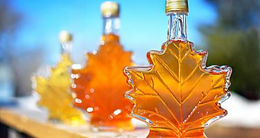 Assorted maple leaf containers of maple syrup