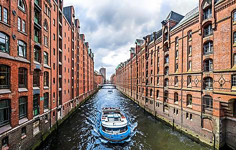 A boat traveling through a canal in the famous Speicherstadt warehouse district in Hamburg, Germany
