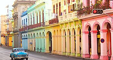 Vintage blue car driving through a colorful street in Havana, Cuba