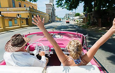 Woman enjoying a drive through Havana in a vintage pink car