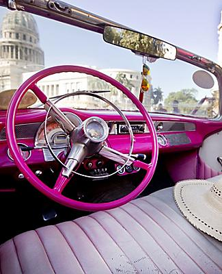 Classic convertible pink taxi parked near the National Capital Building in Havana, Cuba