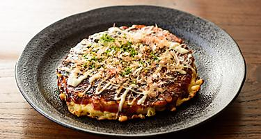 Japenese style pancakes known as Okonomiyaki drizzled with sauce