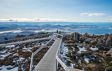 A boardwalk through an icy grassy landscape with views of Hobart, Tasmania