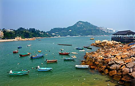 Boats out on the harbor alongside a rocky coast in Hong Kong