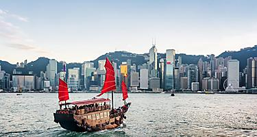 Tourist sailboat crosses Victoria Harbour to the Hong Kong Island with skyscrapers in the background