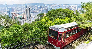 The Victoria peak tram arriving at a station overlooking the skyline in Hong Kong, China