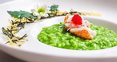 A plate of pesto arugula risotto topped with king crab