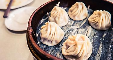 Traditional Taiwan food is steamed dumplings served on a table in a wooden dish with chopsticks