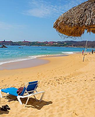 A tiki hut with a pair of tanning chairs out on the beach on Huatulco, Mexico