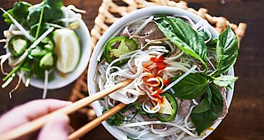 Vietnamese Pho with spicy Sriracha and chopsticks