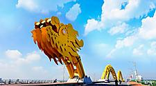A yellow giant dragon bridge on a beautiful cloudy day in Vietnam