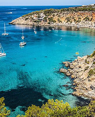 Boats anchored off a secluded beach in Es Verda Island, Ibiza, Spain