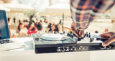 A close up view of a DJ's mixer during an outdoor party