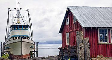 A rustic red Cannery Building with a boat docked in Icy Strait Point, Alaska