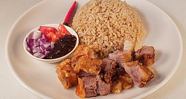 Crispy bagnet, a deep fried crispy pork belly dish, served with onion and fresh tomatoes and a side of rice, in Ilocos, Philippines