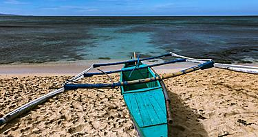 Blue boat docked by the shore in Ilocos, Philippines