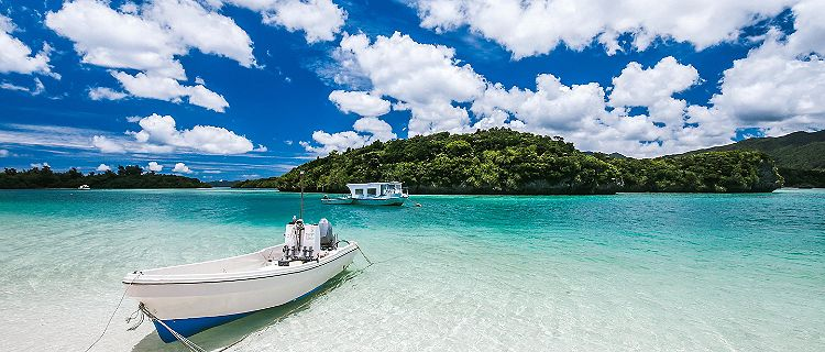 A few boats on the clear water of Kabira Bay in Ishigaki, Japan