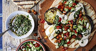 A warm toasted pita bread topped with eggplant, tzaziki sauce, and israeli salad