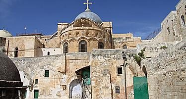Church of the Holy Sepulchre made out of stones with a blue dome and cross over it with blue skies in Jerusalem, Israel