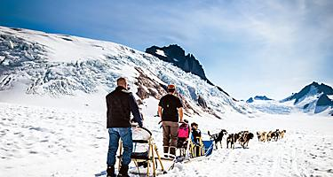 A family out on an excursion of dog sledding with the huskies in the snow in Juneau, Alaska