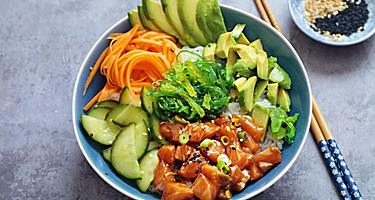 Poke bowl filled with rice, avocado, seaweed salad, veggies, and raw salmon