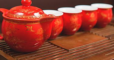 A red tea set with asian designs on a wooden platform in Taiwan