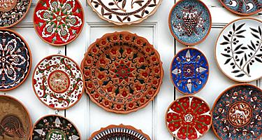 Assorted colorful plates with painted designs hanging on a wall