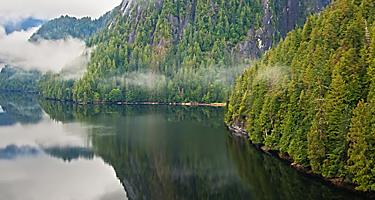 Majestic body of water along the mountains with clouds floating over the water in one of Ketchikan, Alaska's national monuments known as Misty Fjords
