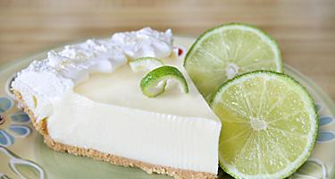 A piece of Key Lime pie with lime slices on the side
