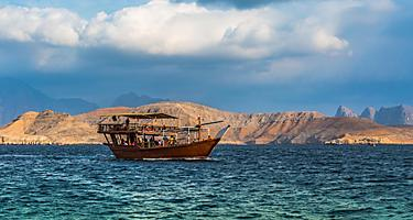 A traditional dhow boat cruising through the water